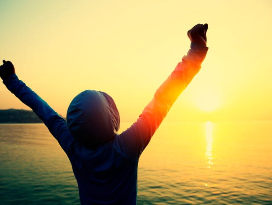 strong confident woman open arms to sunrise at sea