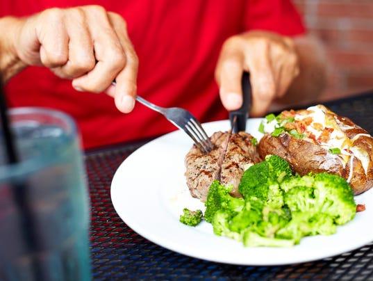 Senior Man Eating Strip Steak At Restaurant Table