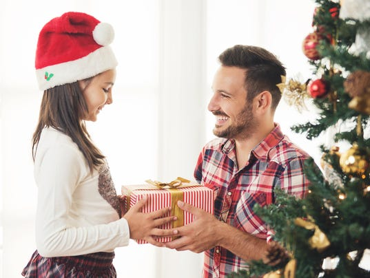 Father and daughter exchanging and opening Christmas presents
