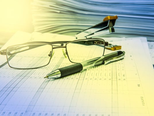 Stack of papers pen Stapler and glasses