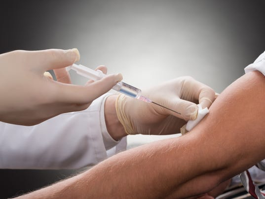 Doctor Injecting Syringe On Patient's Arm