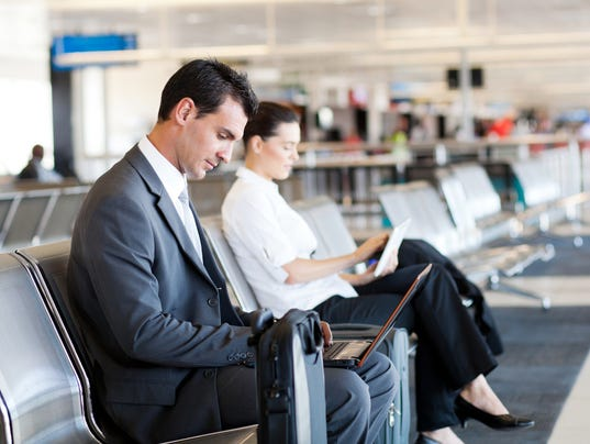 businessman businesswoman using laptop and tablet at airport