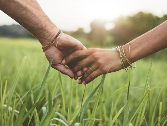 Romantic couple holding hands in a field