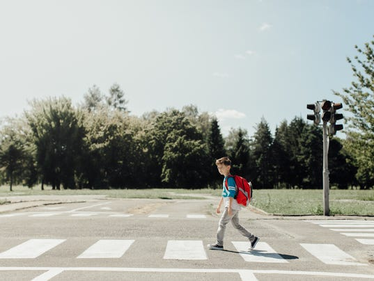 Schoolboy crossing a road on his morning way to school