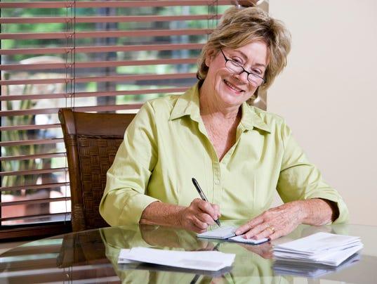 Happy senior woman writing check, paying bills at home