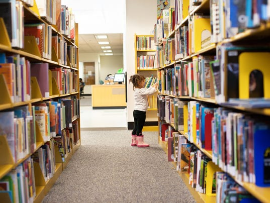 Little Girl At The Library Picking a Book