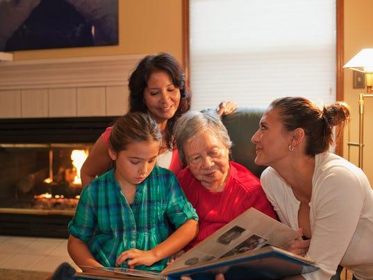 Three generation family looking at photo album