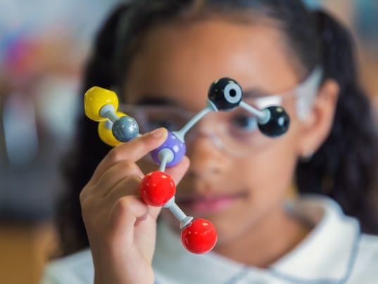 Little girl holding a model of molecular structure