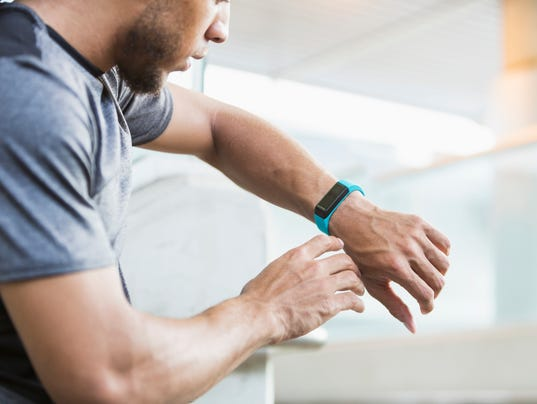 Young mixed race man checking his fitness tracker