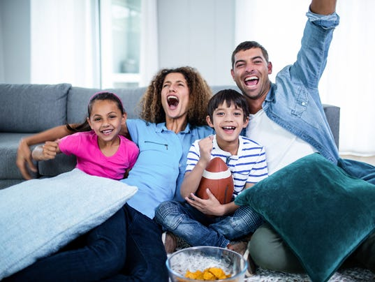 Family watching american football match on television