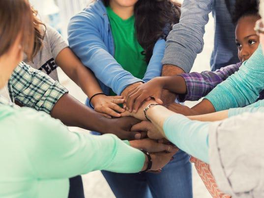 Diverse group of volunteers put hands together