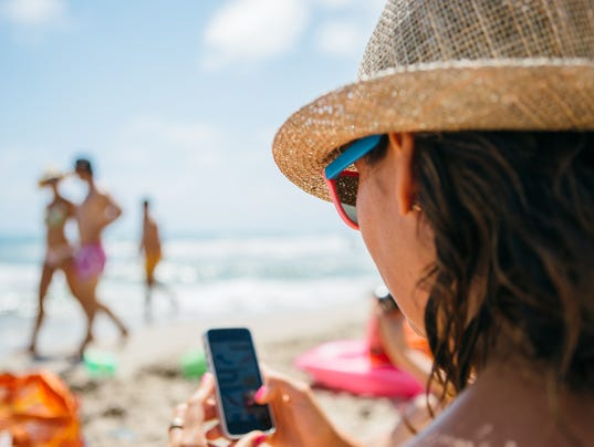 Woman in hat using mobile phone on beach