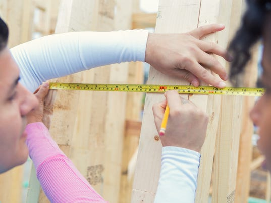 Volunteers measure boards at construction site
