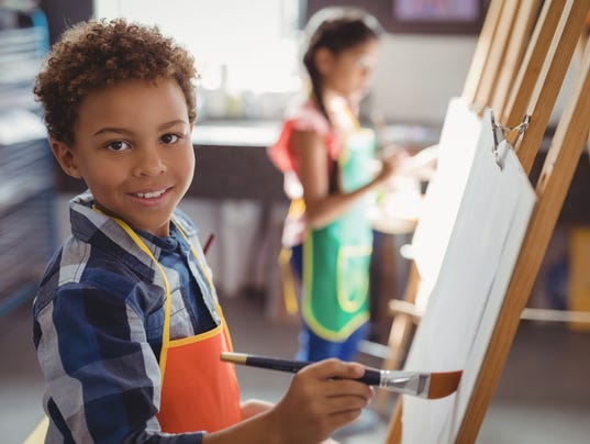 Portrait of smiling schoolboy panting on canvas