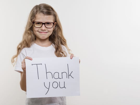 Girl child holding piece of paper with a word THANK YOU. White backgrounde