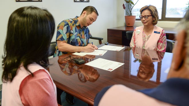 Sen. Michael San Nicloas, center, signs a letter of commitment as Jenny Cruz, Guam Memorial Hospital Volunteers Association president, as other association members look on during a presentation at his office in Hagåtña Jan. 20. San Nicolas announced that with the funds from his $14,403.36 retroactive pay raise, he invested $14,000 of it into an interest-bearing bond. The balance of $403.36 was presented as a donation to GMHVA. The total interest of $6,860, generated by the bond over the investment period, will be donated incrementally to the association, said San Nicolas. When the bond matures in 2023, the association is to receive the initial bond value of $14,000.