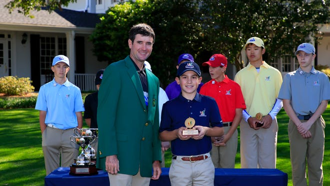 Masters champion Bubba Watson presents Luke Coyle with the Best Putt trophy in the Boys 12-13 age group during the Drive, Chip and Putt National Finals at Augusta National Golf Club, Sunday, April 2, 2017.