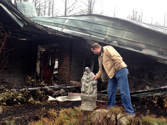 Senior Pastor Kim McCroskey inspects a statue outside the remains of the family life center at Roaring Fork Baptist Church in Gatlinburg on Dec. 6, 2016. The church and the center burned down in wildfires a week earlier.
