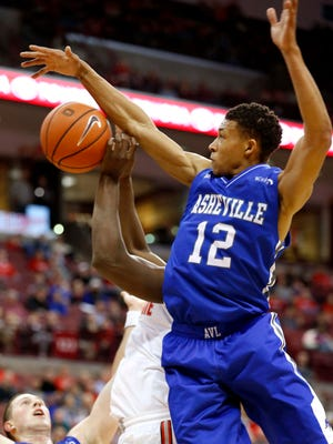 UNC Asheville guard Raekwon Miller (12) blocks the shot of Ohio State Buckeyes forward Jae'Sean Tate (1) during the first half of Thursday's game.