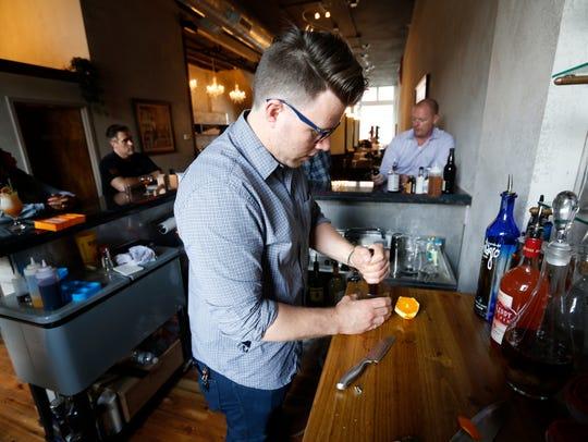 Trevor Daniels mixes a cocktail at Mane Salon & Social