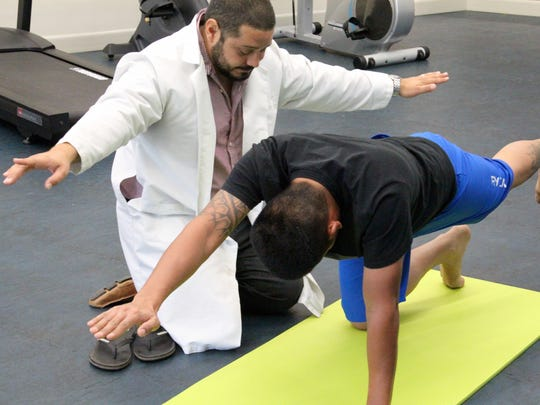In this file photo, Dr. Leonard Campos directs a patient through a series of stretches at NewGen Physical Therapy.