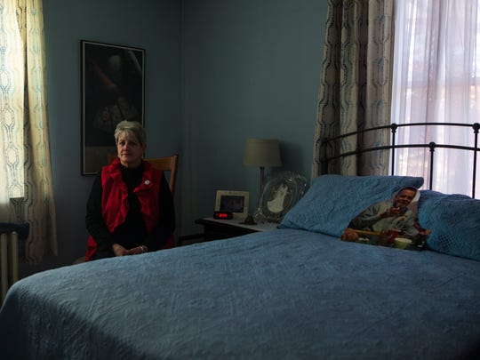 "Lorraine Talarico-Smith sits next to a cutout of her late husband, Thomas ""Smitty"" Smith, that sits on the bed where he used to sleep in their home in Brandywine Hundred. Talarico-Smith says she frequents his room to still say goodnight or talk about her day to him. ""He's not physically here, but I know he can here me up there,"" Talarico-Smith says."