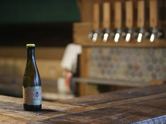 A bottle of Barn Beer rests on the bar at Plan Bee