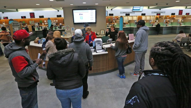 Visitors wait in line at the Delaware Division of Motor Vehicles service center near New Castle on Monday. The DMV has a new kiosk for motorists to pay fines.
