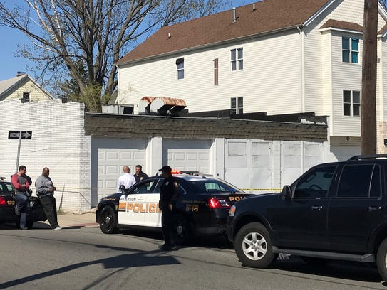 Police search a home near the scene of a shooting in