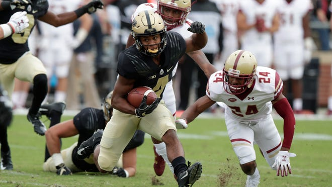 FILE - In this Sept. 22, 2018, file photo, Purdue wide receiver Rondale Moore (4) runs past Boston College defensive back Taj-Amir Torres (24) during the first half of an NCAA college football game, in West Lafayette, Ind. Nebraska's Adrian Martinez and Purdue's Rondale Moore lead the list of the conference's top rookies. (AP Photo/Michael Conroy, File)