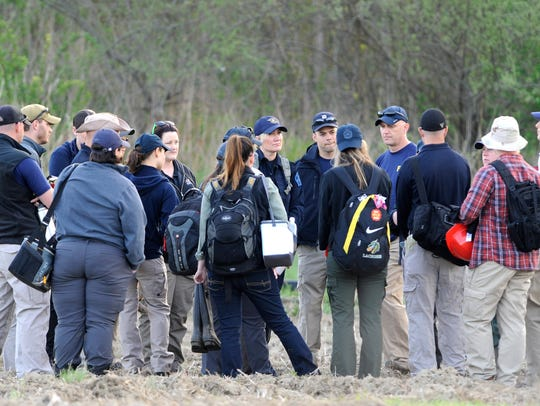 Investigators huddle before they travel across a huge field to the dig site at the end of Cranberry Creek Drive in the 23 Mile and North Avenue area in Macomb Township on May 9, 2018.