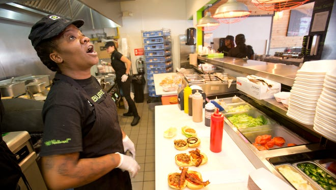 In this Tuesday, Jan. 27, 2015 photo, BurgerFi restaurant employee Nathali Dorvil calls out an order as Elia Carranza, rear, mans the grill at the Aventura, Fla., restaurant. The company plans to nearly double in size from their existing 65 restaurants this year. (AP Photo/Wilfredo Lee)