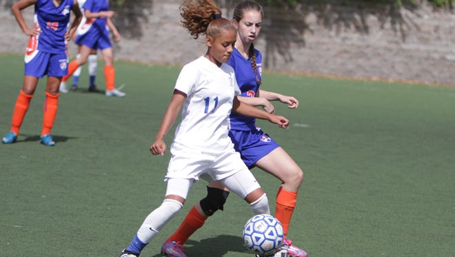Saunders' Zhane Jacinto (white) battles for possession of the ball against Yonkers' Jessica Oliveira during the Yonkers tournament final at Tibbetts Park on Saturday, September 26, 2015. Saunders won 3-1.