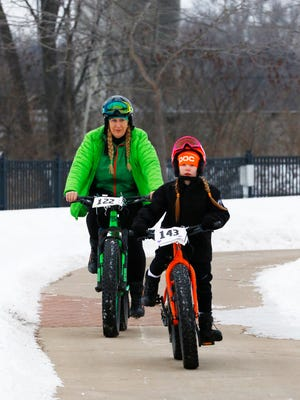 Siobhan Artz, and her mother, Christine Kysely of Wausau, ride fat-tire bikes on the River Edge Trail behind the Marathon County Public Library in downtown Wausau.