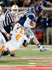 Mississippi quarterback Bo Wallace (14) runs through a tackle attempt by Tennessee defensive back Todd Kelly Jr. (6)