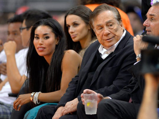 FILE - In this file photo taken on Friday, Oct. 25, 2013, Los Angeles Clippers owner Donald Sterling, right, and V. Stiviano, left, watch the Clippers play the Sacramento Kings during the first half of an NBA basketball game in Los Angeles. Used car dealership chain CarMax says it is ending its sponsorship of the Clippers in the wake of racist comments attributed to Sterling. (AP Photo/Mark J. Terrill, File)