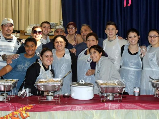 Iris Garcia, center, behind the crockpot, and Armand Paganelli, behind her, have been fulfilling Iris's promise to God every year for 25 years, feeding hundreds of hungry people in the gym of P.S 51 in The Bronx.