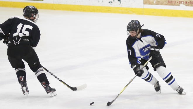 St. Mary's Springs Academy hockey's Jack Sabel works the puck down the ice against West Bend West's Riley McClarran during their game Thursday February 15, 2018 at the Blue Line Family Ice Center in Fond du Lac.