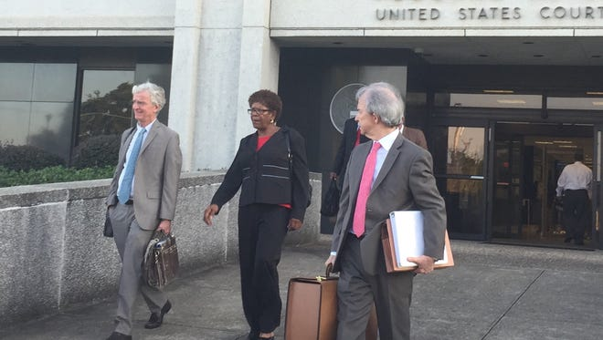 Linda Bolton leaves the William M. Colmer Federal Courthouse with attorneys Robert McDuff, left, and Ben Galloway.