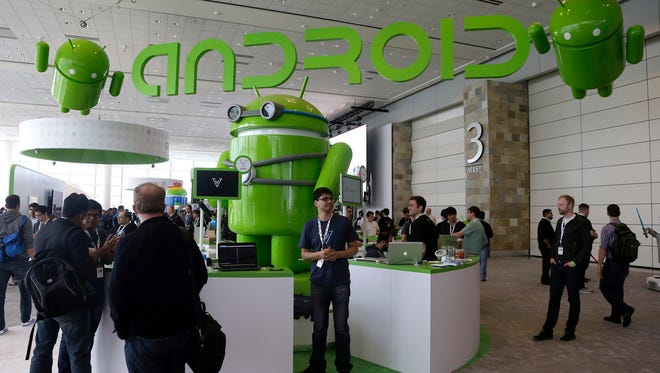 Visitors walk past the Android booth on the floor at Google I/O 2013 in San Francisco last year.