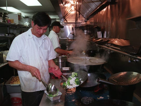 Chef Woontung Wong packs a takeout order at Eden Wok,