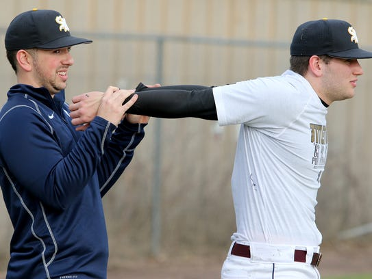 South Kitsap's Drew Worden (left) helps Alex Garcia stretch during a recent practice at Elton Goodwin Field.