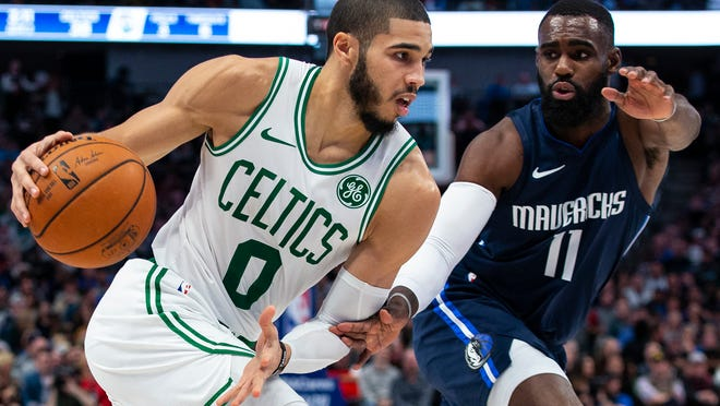 Boston Celtics forward Jayson Tatum (0) controls the ball as Dallas Mavericks guard Tim Hardaway Jr. (11) defends during the first half of an NBA basketball game Wednesday, Dec. 18, 2019, in Dallas.