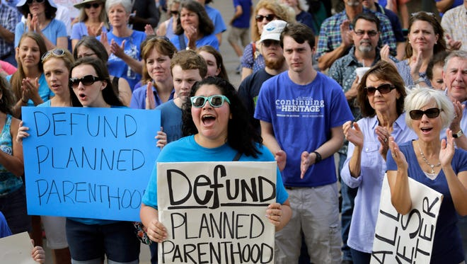 FILE - In this July 28, 2015, file photo, Erica Canaut, center, cheers as she and other anti-abortion activists rally on the steps of the Texas Capitol in Austin, Texas, to condemn the use in medical research of tissue samples obtained from aborted fetuses. Texas announced Monday, Oct. 19, 2015, that it was cutting off Medicaid funding to Planned Parenthood clinics following undercover videos of officials discussing fetal tissue, potentially triggering a legal fight like the one unfolding in neighboring Louisiana. (AP Photo/Eric Gay, File)