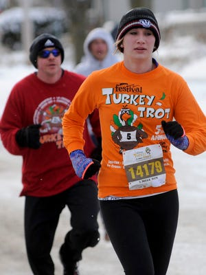 Regina Bushman of Manitowoc heads for the 5k finish line in the 7th annual Festival Foods Turkey Trot at Red Arrow Park on Thanksgiving, Thursday, Nov. 27, 2014 in Manitowoc.  Matthew Apgar/HTR Media