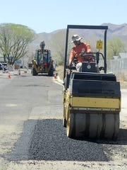 Public Works Director Jay Flakus uses a roller to smooth