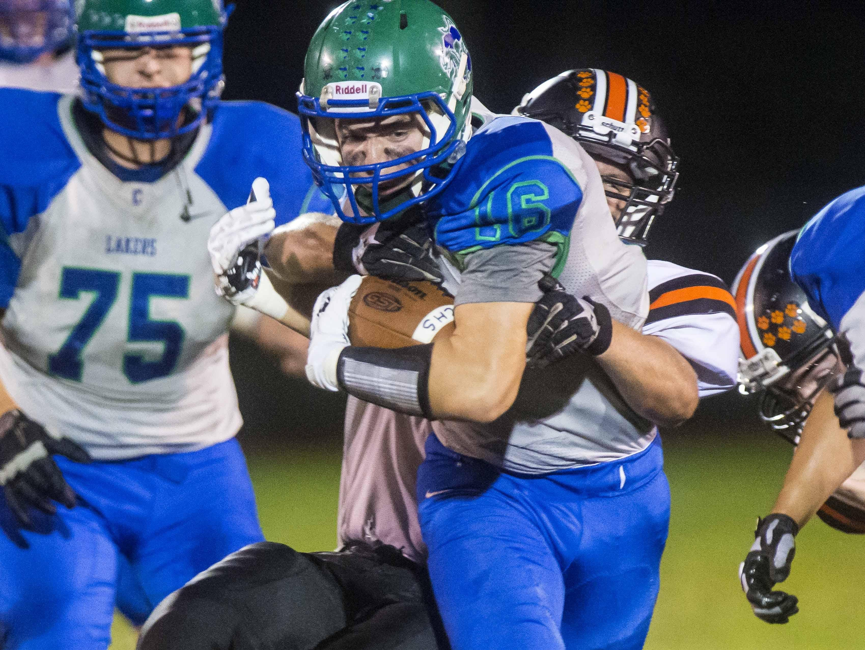 Colchester's Dakota Navari, front, is pulled down by Middlebury's Chris Grier in Colchester on Friday, September 18, 2015.