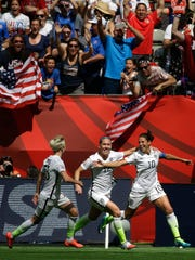 From left, United States' Megan Rapinoe, Lauren Holiday and Carli Lloyd celebrate after Lloyd scored her second goal of the match against Japan during the first half of the FIFA Women's World Cup soccer championship in Vancouver, British Columbia.