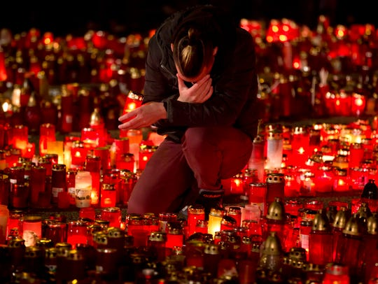 A man touches his forehead holding a candle outside