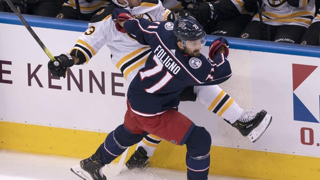 The Bruins' Brad Marchand is run into the boards by Columbus Blue Jackets forward Nick Foligno during the first period of their exhibition game Thursday night in Toronto. Marchand would leave the game in the third period with what appeared to be a lower-body injury.
